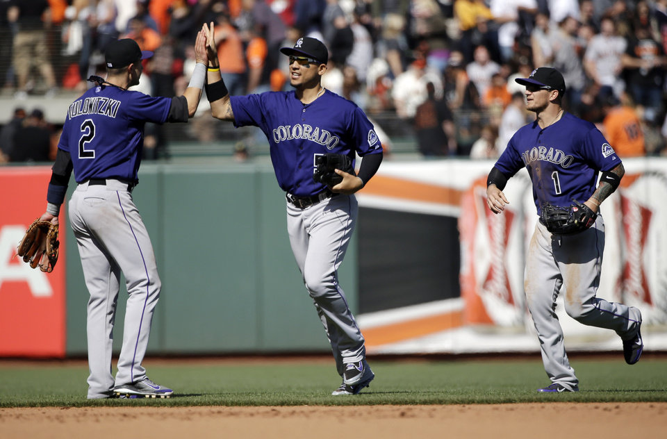 Photo - Colorado Rockies' Troy Tulowitzki (2), Carlos Gonzalez, center, and Brandon Barnes (1) celebrate a 1-0 win over the San Francisco Giants in a baseball game on Saturday, April 12, 2014, in San Francisco. (AP Photo/Marcio Jose Sanchez)