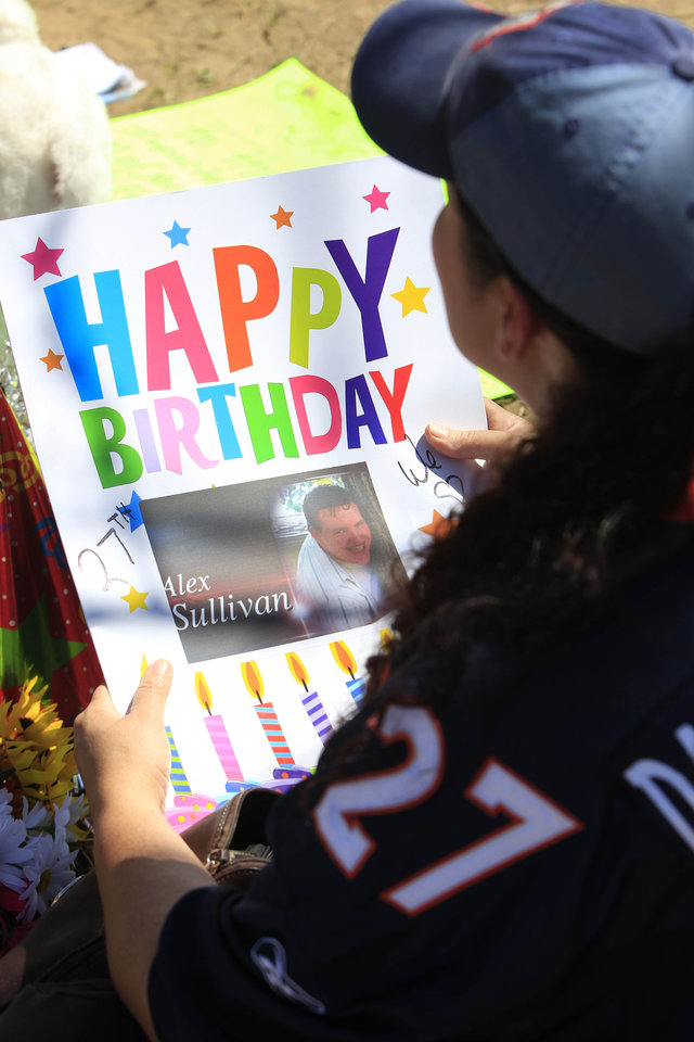 Photo -   Shelly Fradkin, the mother of a friend of shooting victim Alex Sullivan, holds a birthday card for Sullivan as she places the card at a makeshift memorial near the movie theater on Saturday, July 21, 2012 in Aurora, Colo. Twelve people were killed and dozens were injured in the attack early Friday at the packed theater during a showing of the Batman movie,