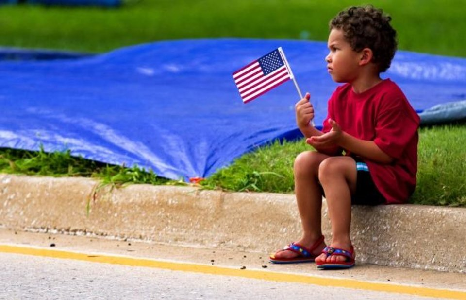 Photo -  Levi Gilkey, 3, waves his American flag Thursday as he waits for the start of the Bethany Freedom Festival parade.    [Chris Landsberger/The Oklahoman]