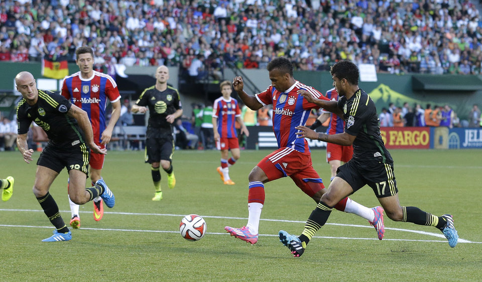 Photo - Bayern Munich's Julian Green, second from right, shoots as Seattle Sounders' DeAndre Yedlin, right, defends during the first half of the MLS All-Star soccer game, Wednesday, Aug. 6, 2014, in Portland, Ore. (AP Photo/Ted S. Warren)