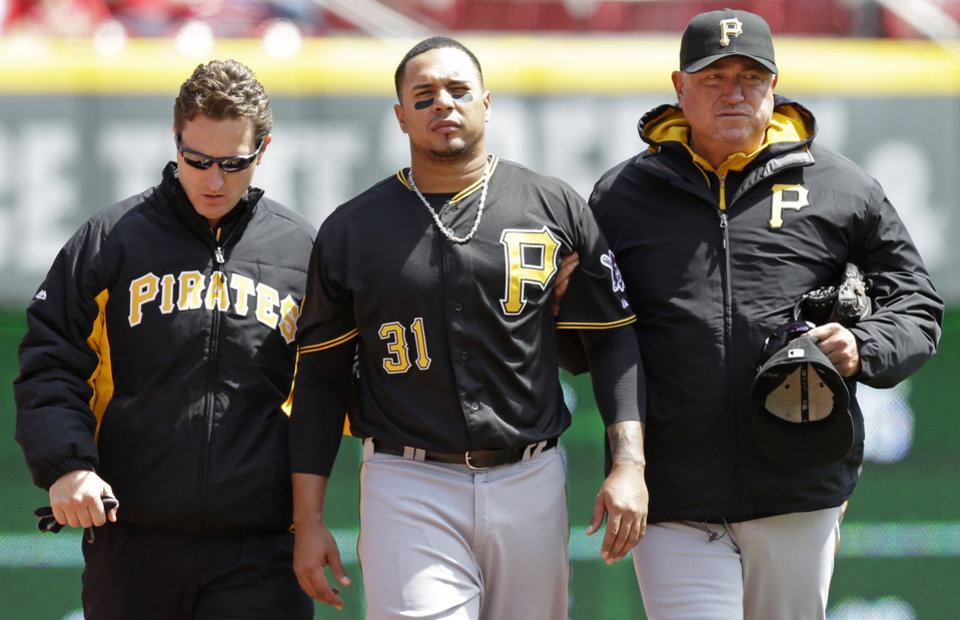 Photo - Pittsburgh Pirates right fielder Jose Tabata (31) is helped off the field by manager Clint Hurdle, right, after Tabata ran into the left field wall catching a fly ball hit by Cincinnati Reds' Brayan Pena in the fifth inning of a baseball game, Wednesday, April 16, 2014, in Cincinnati. Tabata was replaced by Starling Marte. Cincinnati won 4-0. (AP Photo/Al Behrman)