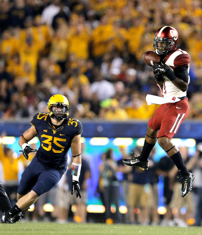 Photo - Oklahoma's K.J. Young (1) makes a catch in front of West Virginia's Nick Kwiatkoski (35) during the college football game between West Virginia  Mountaineers and the University of Oklahoma Sooners at Milan Puskar Stadium in Morgantown, W.Va., Saturday, Sept. 20, 2014. Photo by Sarah Phipps, The Oklahoman