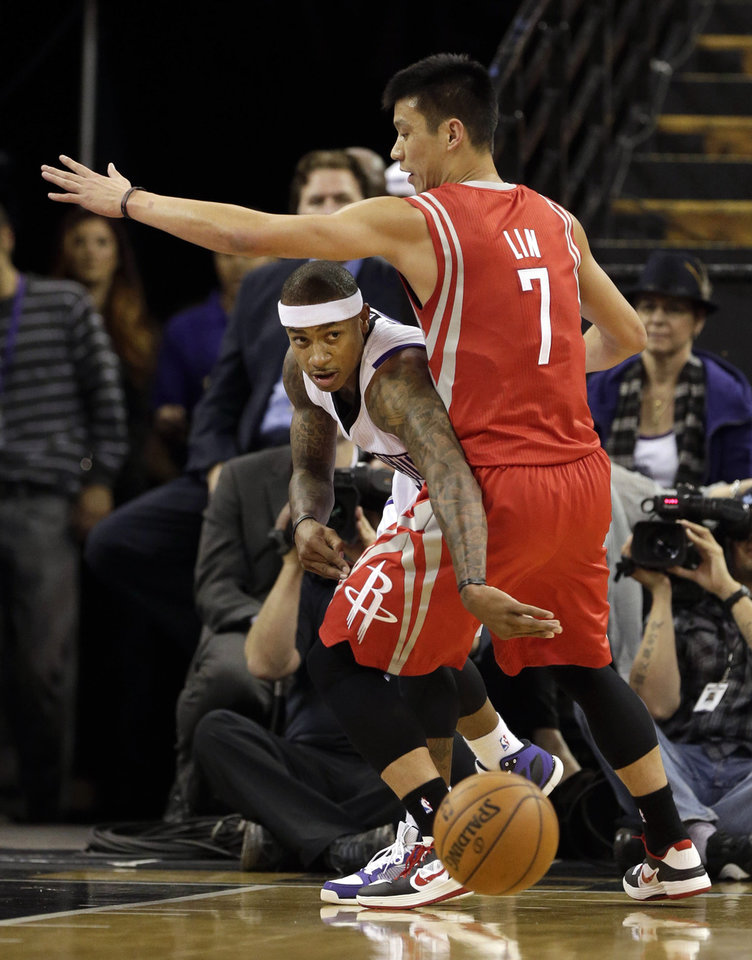 Photo - Sacramento Kings guard Isaiah Thomas, left, ducks under the arm of Houston Rockets guard Jeremy Lin to pass off during the first quarter of an NBA basketball game in Sacramento, Calif., Sunday, Feb. 10, 2013.(AP Photo/Rich Pedroncelli)