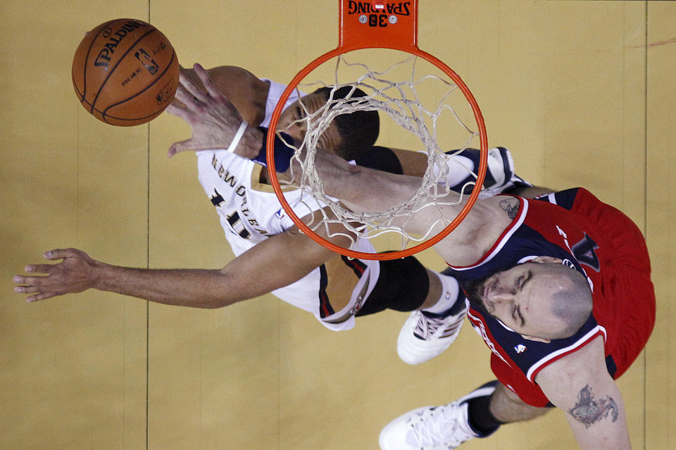 Photo - New Orleans Pelicans shooting guard Eric Gordon (10) is fouled by Washington Wizards center Marcin Gortat (4) as he goes to the basket in the first half of an NBA basketball game in New Orleans, Wednesday, Jan. 8, 2014. (AP Photo/Gerald Herbert)