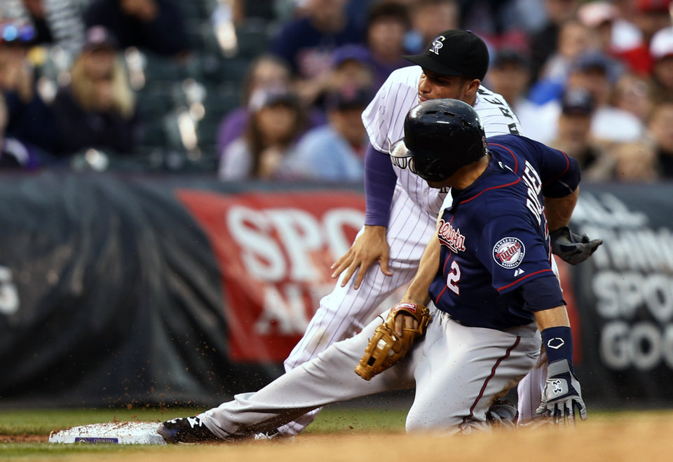 Photo - Colorado Rockies third baseman Nolan Arenado (28) applies the tag to Minnesota Twins' Brian Dozier (2) during the third inning of a baseball game on Friday, July 11, 2014, in Denver. (AP Photo/Jack Dempsey)