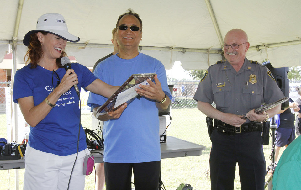 Photo - Dr. R. Murali Krishna (center) presents awards to Actress Stacey Logan-Lewis and OKC Police Cpt. Robert Nash before the start of the NAMI (National Alliance on Mental Illness) walk at Stars and Stripes Park in Oklahoma City, OK, to raise money for mental illness causes, Saturday, May 19, 2012,  By Paul Hellstern, The Oklahoman