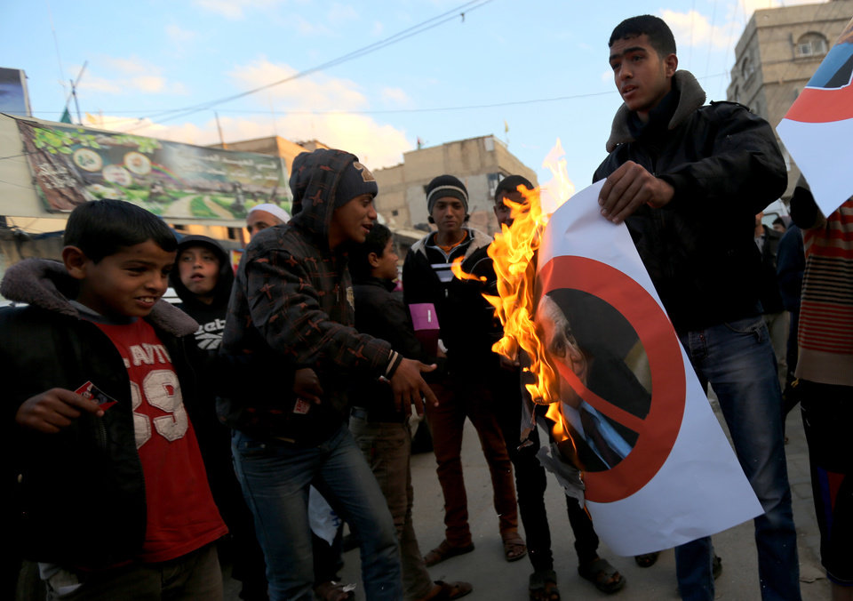 Photo - Palestinians burn a poster of the former Prime Minister Ariel Sharon in Khan Younis, southern Gaza Strip, Saturday, Jan. 11, 2014. Sharon was loathed by many Palestinians as a bitter enemy who did his utmost to sabotage their independence hopes — by leading military offensives against them in Lebanon, the West Bank and Gaza and a settlement drive on the lands they want for a state. Sharon died Saturday, eight years after a debilitating stroke put him into a coma. He was 85. (AP Photo/Hatem Moussa)