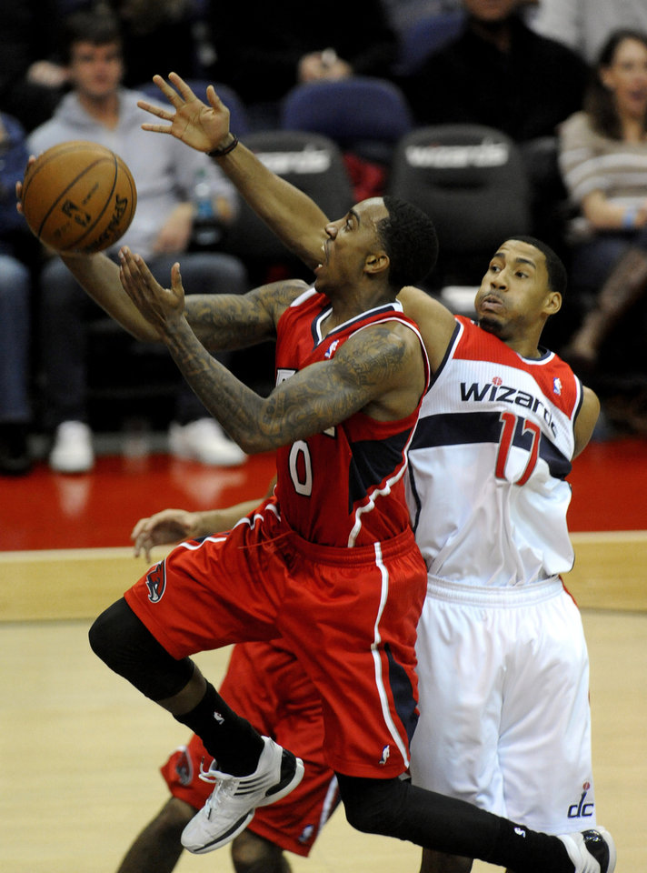 Atlanta Hawks guard Jeff Teague (0) drives to the basket to score against the defense of Washington Wizards guard Garrett Temple (17) during the first half of their NBA basketball game on Saturday, Jan. 12, 2013, in Washington. (AP Photo/Richard Lipski)