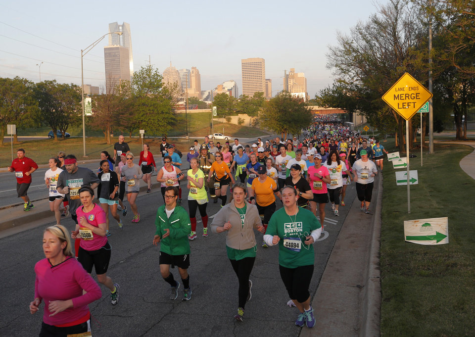 Photo - Runners make their way east on NE 4th St. during the Oklahoma City Memorial Marathon in Oklahoma City, Sunday, April 28, 2013.  Photo by Garett Fisbeck, For The Oklahoman