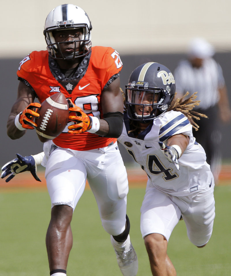 Photo - Oklahoma State's James Washington (28) makes a catch in front of Pittsburgh's Avonte Maddox (14) during a college football game between the Oklahoma State Cowboys (OSU) and the Pitt Panthers at Boone Pickens Stadium in Stillwater, Okla., Saturday, Sept. 17, 2016. Photo by Chris Landsberger, The Oklahoman