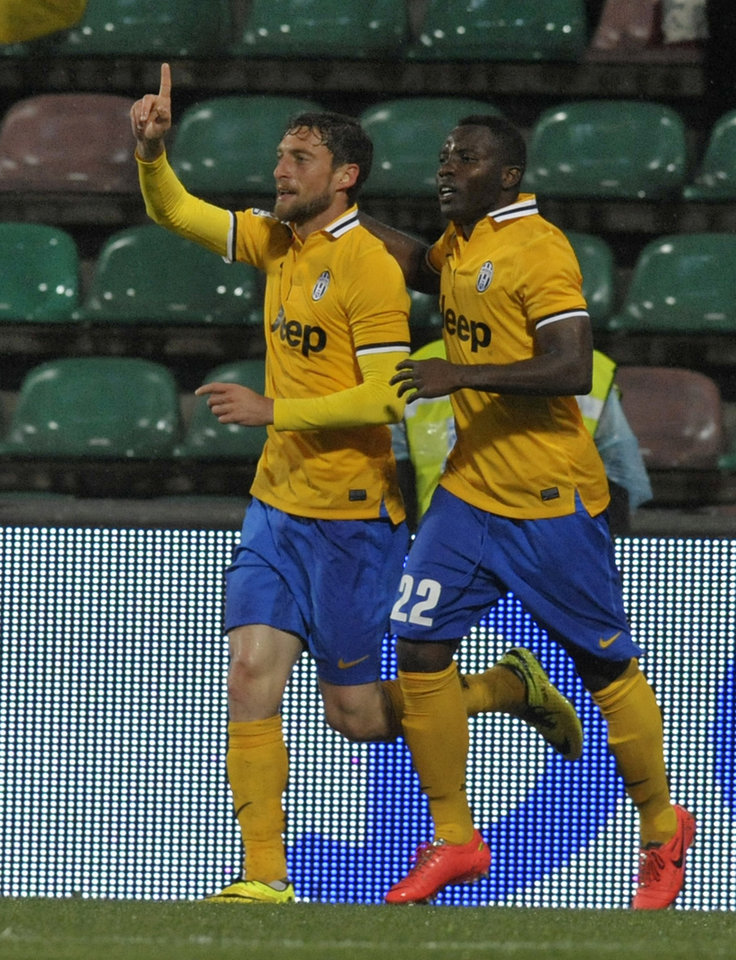 Photo - Juventus's Claudio Marchisio, left, celebrates with his teammate Kwadwo Asamoah of Ghana after scoring against Sassuolo during their Italian Serie A soccer match at Mapei stadium in Reggio Emilia, Italy, Monday, April 28, 2014. (AP Photo/Marco Vasini)