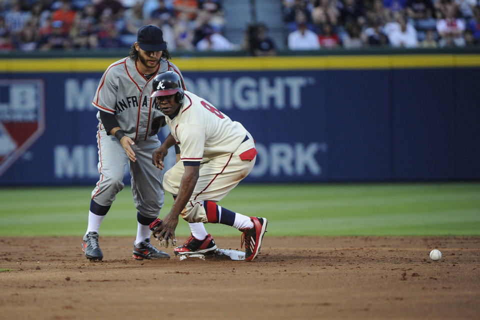 Photo - Atlanta Braves' Justin Upton (8) comes up safe at second base after San Francisco Giants shortstop Brandon Crawford could not handle the throw after Evan Gattis reached on a force attempt during the second inning of a baseball game, Saturday, May 3, 2014, in Atlanta. (AP Photo/John Amis)