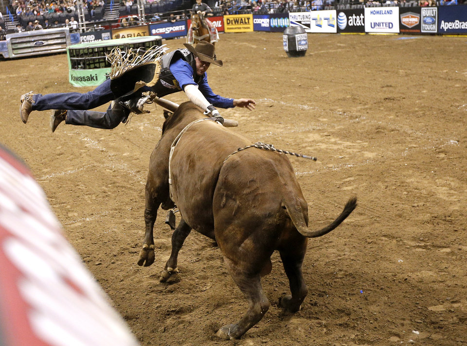 Emilio Resende rides Redneck during the Express Employment Professionals Invitational PBR  event at the Chesapeake Energy in Oklahoma City, Saturday, Jan. 25, 2014.  Photo by Sarah Phipps, The Oklahoman