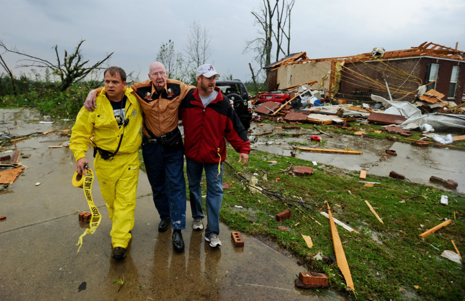 Photo - Deputy Johnny Morell and Kirk Bowley escort John Wessinger from the remains of his home in the McCulley Mill Rd. area near Athens, Ala., following a large tornado that cut a path through Lawrence, Morgan and Limestone Counties Wednesday, April 27, 2011. Wessinger suffered an arm injury as well as cuts and scrapes.  (AP Photo/The Decatur Daily, Gary Cosby Jr.)