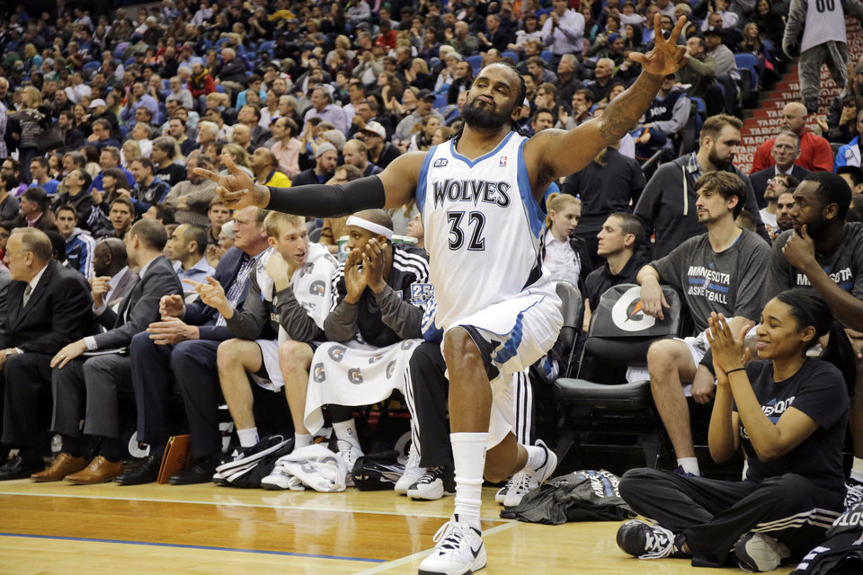 Photo - Minnesota Timberwolves center Ronny Turiaf (32), of France, reacts after teammate Ricky Rubio made a three-point basket during the second quarter of an NBA basketball game against the Utah Jazz in Minneapolis, Wednesday, April 16, 2014. (AP Photo/Ann Heisenfelt)