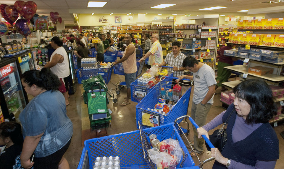 Photo - Hundreds of Oahu residents flocked to the Times Supermarket to purchase water and supplies Thursday, March 10, 2011 in Honolulu. The state of Hawaii is under a tsunami warning due to a large 8.9 earthquake off Japan. The earthquake is believed to have generated a tsumani wave. The Pacific Tsunami Center expects the wave to hit Hawaii at 2:59 a.m. Hawaiian Standard Time. (AP Photo/Eugene Tanner) ORG XMIT: HIET104