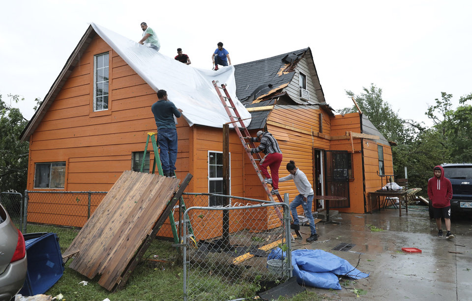 Photo - A crew puts a tarp on a home after storm damaged it near Newton and North Rockford in Tulsa, Okla., on Tuesday, May 21, 2019. (Tom Gilbert/Tulsa World via AP)