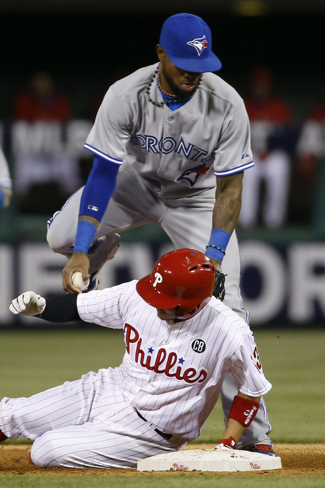 Photo - Philadelphia Phillies' Freddy Galvis, bottom, collides with Toronto Blue Jays shortstop Jose Reyes after being forced out at second base on a fielders choice by Chase Utley  during the third inning of an interleague baseball game, Monday, May 5, 2014, in Philadelphia. (AP Photo/Matt Slocum)