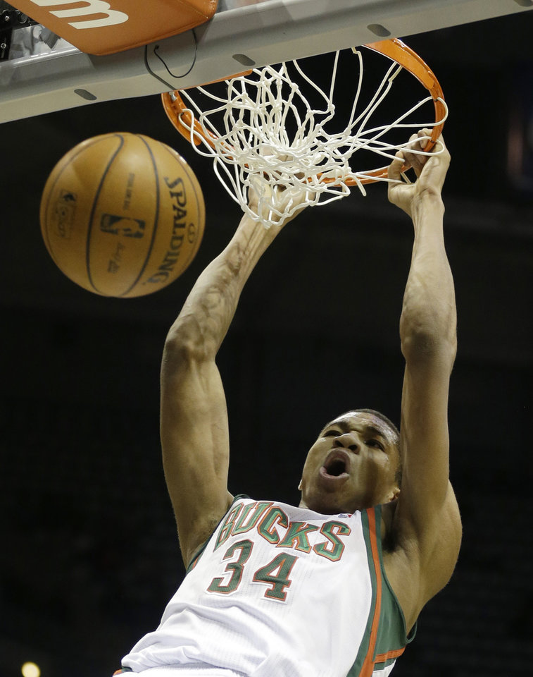 Photo - Milwaukee Bucks' Giannis Antetokounmpo dunks against the Phoenix Suns during the second half of an NBA basketball game Wednesday, Jan. 29, 2014, in Milwaukee. (AP Photo/Jeffrey Phelps)