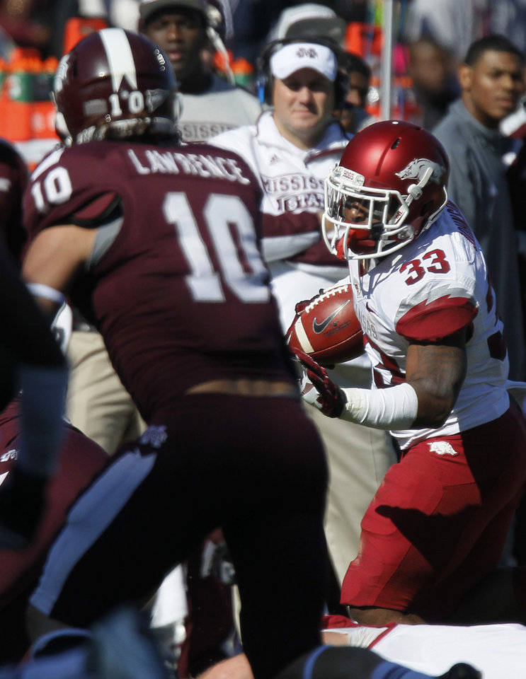 Photo -   Arkansas running back Dennis Johnson (33) runs up field at Mississippi State linebacker Cameron Lawrence (10) chases in the second quarter of their NCAA college football game in Starkville, Miss., Saturday, Nov. 17, 2012. (AP Photo/Rogelio V. Solis)
