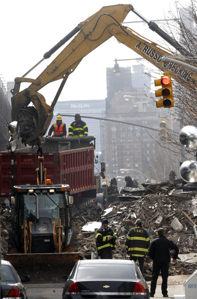 Photo - Debris is removed from a mound of rubble a day after a gas leak-triggered explosion, Thursday, March 13, 2014, in East Harlem, New York. Rescuers working amid gusty winds, cold temperatures and billowing smoke pulled additional bodies Thursday from the rubble of two apartment buildings that collapsed Wednesday. (AP Photo/Julio Cortez)