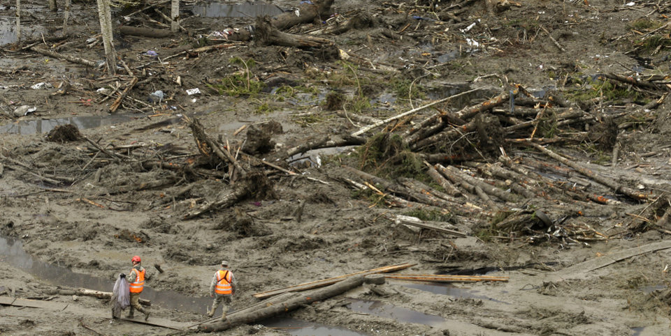 Photo - A worker carries a recovered item along a plywood walkway through other debris, Sunday, March 30, 2014, as search work continues at the site of the massive mudslide that struck the community of Oso,Wash. on March 22, 2014. (AP Photo/Ted S. Warren)