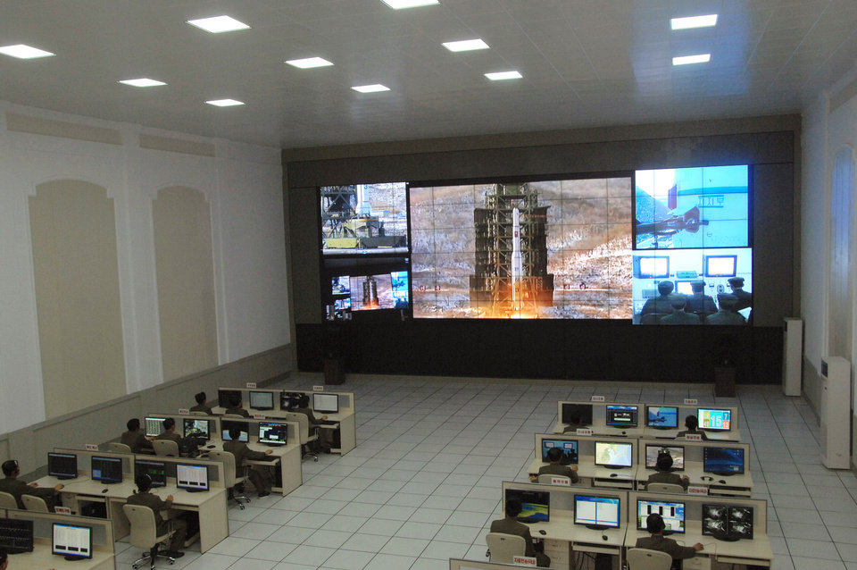 Scientists and technicians at the General Satellite Control and Command Center on the outskirts of Pyongyang watch the launch of the Unha-3 rocket from a launch site on the west coast, in the village of Tongchang-ri, about 56 kilometers (35 miles) from the Chinese border city of Dandong, North Korea, Wednesday, Dec. 12, 2012. North Korea successfully fired the long-range rocket on Wednesday, defying international warnings as the regime of Kim Jong Un took a big step forward in its quest to develop a nuclear missile. (AP Photo) ORG XMIT: PYO109