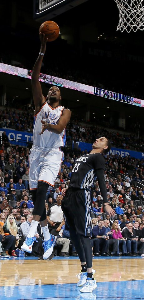 Photo - Oklahoma City's Kevin Durant (35) goes past Minnesota's Kevin Martin (23) during an NBA basketball game between the Oklahoma CIty Thunder and the Minnesota Timberwolves at Chesapeake Energy Arena in Oklahoma City, Wednesday, Feb. 5, 2014. Photo by Bryan Terry, The Oklahoman
