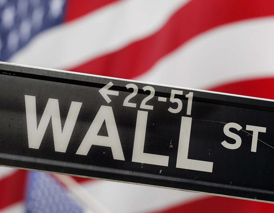 Photo - FILE - In this Aug. 7, 2006 file photo, a Wall Street street sign is seen in front of flags at the New York Stock Exchange. Stocks rose in early trading Wednesday, Dec. 16, 2006, following a benign reading on consumer inflation and a rebound in housing starts. (AP Photo/Mark Lennihan, File) ORG XMIT: NYBZ110