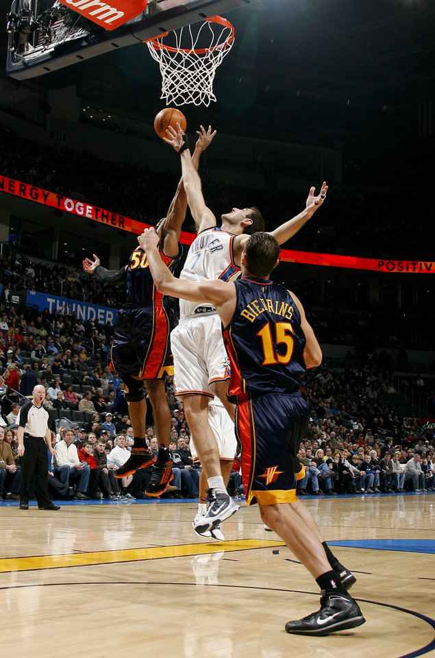 Photo - Oklahoma City's Nenad Krstic (12) grabs a rebound as Golden State's Corey Maggette (50) and Andris Biedrins (15) defend during the NBA game between the Oklahoma City Thunder and Golden State Warriors, Sunday, Jan. 31, 2010, at the Ford Center in Oklahoma City. Photo by Sarah Phipps, The Oklahoman