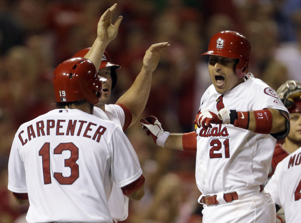 Photo - St. Louis Cardinals' Allen Craig, right, is congratulated by teammates Matt Carpenter (13) and Matt Holliday after hitting a grand slam during the seventh inning of a baseball game against the Cincinnati Reds Monday, Aug. 26, 2013, in St. Louis. (AP Photo/Jeff Roberson)
