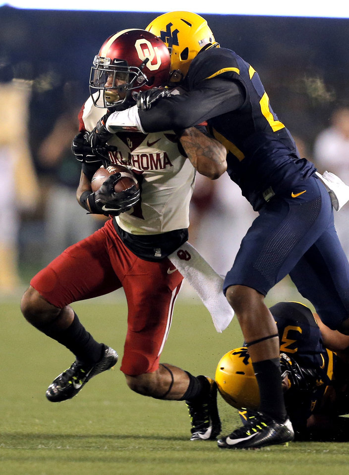 Photo - Oklahoma's K.J. Young (1) is wrapped up by West Virginia's Jeremy Tyler (24) during the college football game between West Virginia  Mountaineers and the University of Oklahoma Sooners at Milan Puskar Stadium in Morgantown, W.Va., Saturday, Sept. 20, 2014. Photo by Sarah Phipps, The Oklahoman
