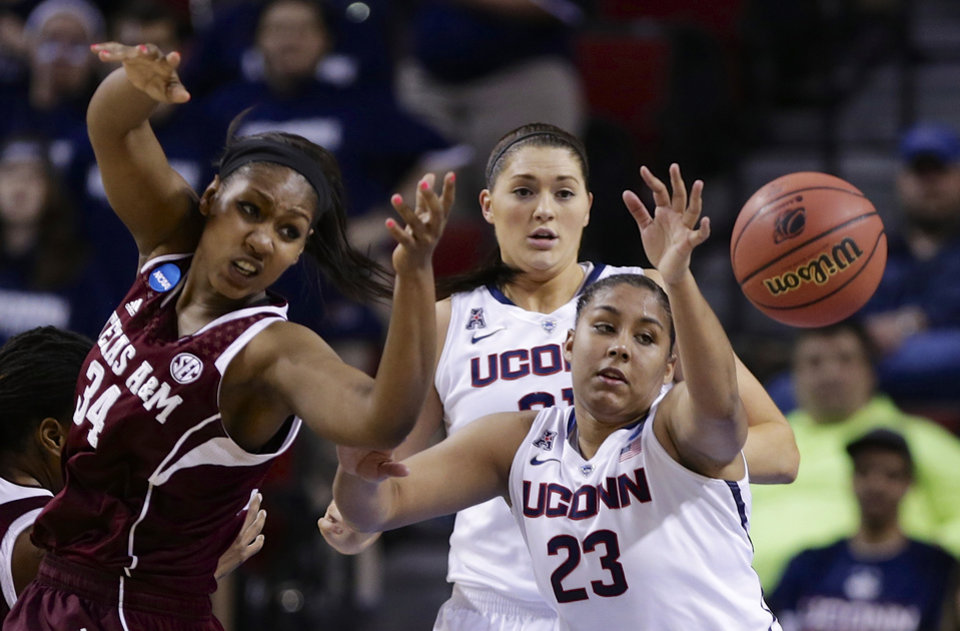 Photo - Texas A&M's Karla Gilbert (34), Connecticut's Kaleena Mosqueda-Lewis (23) and Connecticut's Stefanie Dolson, center rear, go for a rebound during the first half of a regional final game in the NCAA college basketball tournament in Lincoln, Neb., Monday, March 31, 2014. (AP Photo/Nati Harnik)