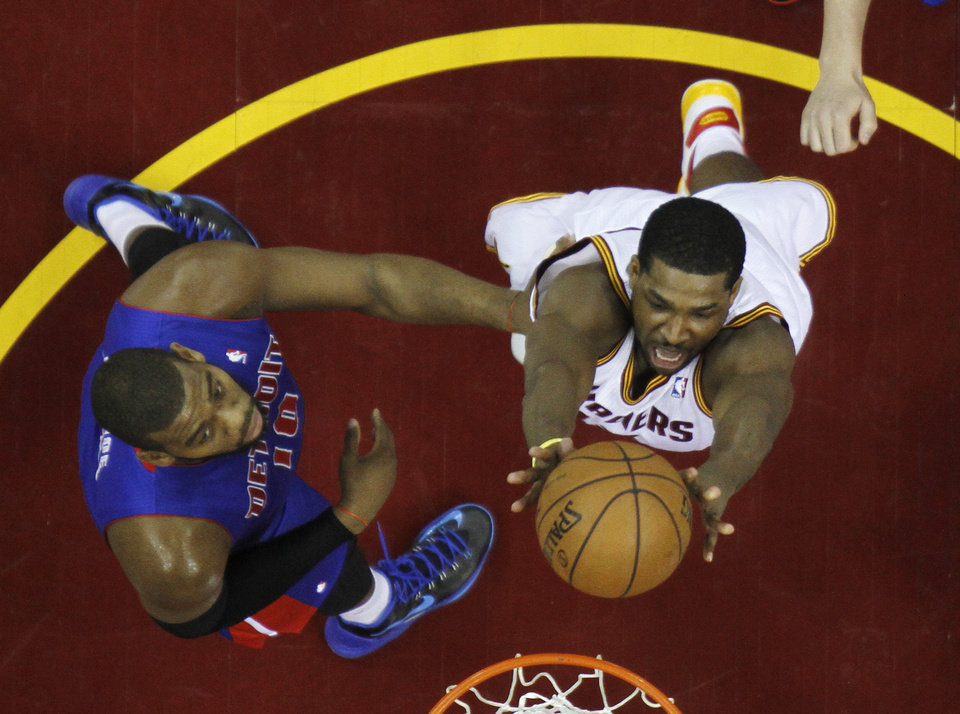 Photo - Cleveland Cavaliers' Tristan Thompson, right, shoots inside Detroit Pistons' Greg Monroe (10) in the first half of an NBA basketball game on Wednesday, April 10, 2013, in Cleveland. (AP Photo/Mark Duncan)