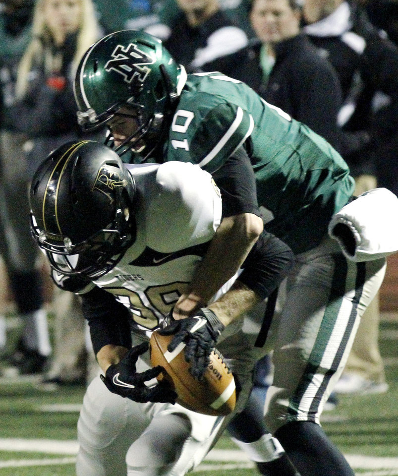 Photo - Norman North's Carter Klein strips the ball from receiver Nathan Caty after a reception in the first quarter as Broken Arrow plays Norman North in class 6A football on Friday, Nov. 16, 2012 in Norman, Okla.  The ball was recovered by the Timberwolves.  Photo by Steve Sisney, The Oklahoman