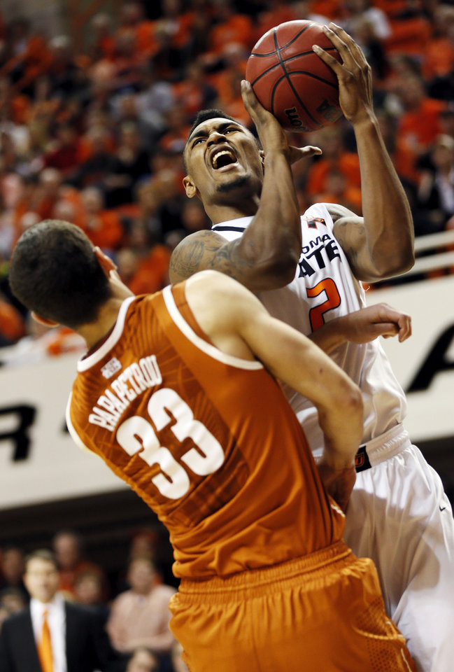Photo - Oklahoma State's Le'Bryan Nash (2) collides with Texas' Ioannis Papapetrou (33) during a men's college basketball game between Oklahoma State University and the University of Texas at Gallagher-Iba Arena in Stillwater, Okla., Saturday, March 2, 2013. Nash was called for a foul on the play. OSU won, 78-65. Photo by Nate Billings, The Oklahoman