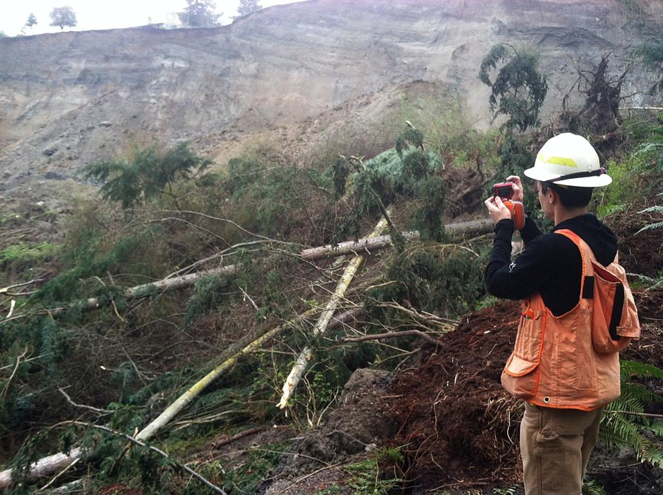 This March 27, 2013 photo provided by the Washington Dept. of Natural Resources, DNR geologist Stephen Slaughter takes photographs of a massive landslide that damaged one home and isolated or threatened more than 30 others near Coupeville, Wash.  Geologists and engineers are assessing what might happen next after a large landside thundered down the scenic island hillside overlooking Puget Sound. (AP Photo/Washington Dept. of Natural Resources, Isabelle Sarikhan)