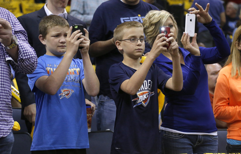 Photo - Nate Kerley, 14, left, Ryan Wright, 13, and his mother Aleatha Wright of Vienna, Illinios take photos of the Thunder before during Game 6  in the first round of the NBA playoffs between the Oklahoma City Thunder and the Memphis Grizzlies at FedExForum in Memphis, Tenn., Thursday, May 1, 2014. Photo by Bryan Terry, The Oklahoman