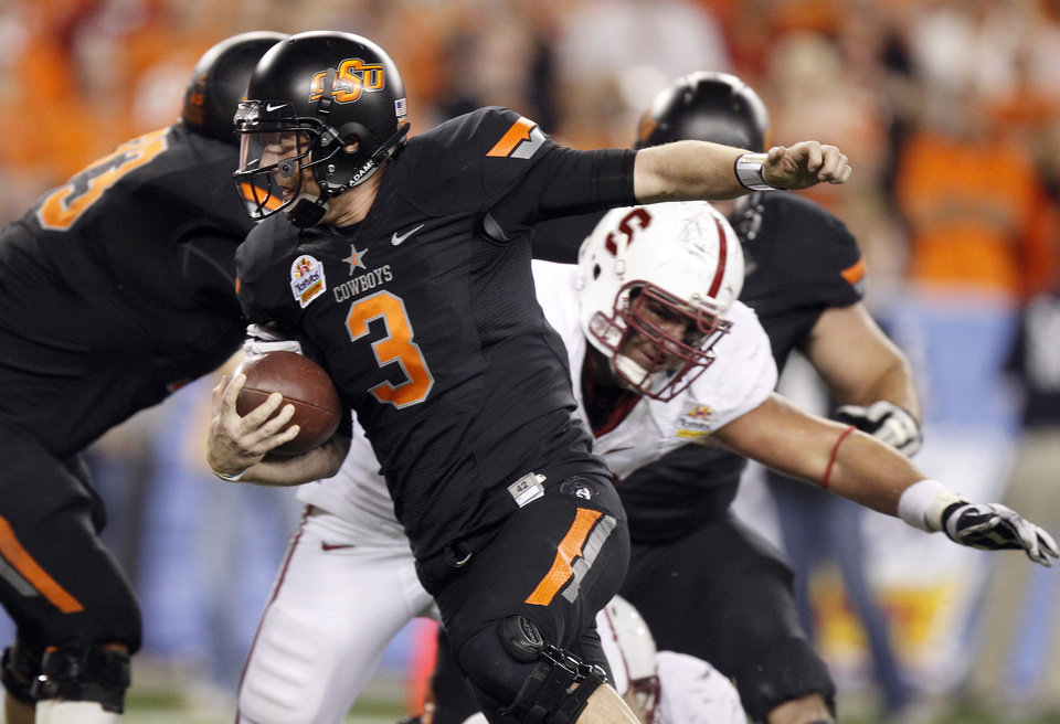 Photo - Oklahoma State quarterback Brandon Weeden, left, breaks away from the tackle attempt by Stanford defensive end Ben Gardner, right, as Weeden rushes for a touchdown during the first half of the Fiesta Bowl NCAA college football game Monday, Jan. 2, 2012, in Glendale, Ariz. (AP Photo/Paul Connors)