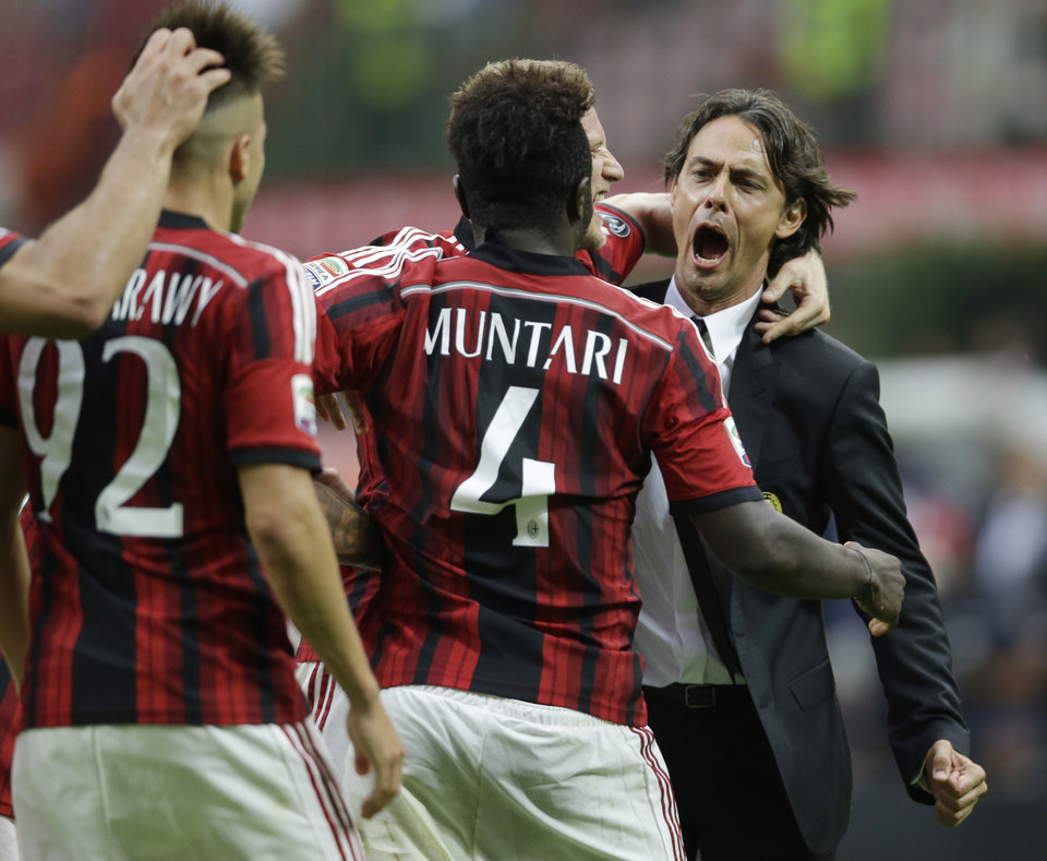 Photo - AC Milan midfielder Sulley Muntari, of Ghana, back to camera, celebrates with AC Milan coach Filippo Inzaghi after scoring his side's second goal during a Serie A soccer match between AC Milan and Lazio, at the San Siro stadium in Milan, Italy, Sunday, Aug. 31, 2014. (AP Photo/Luca Bruno)