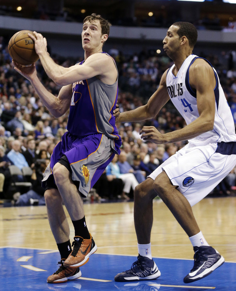 Photo - Phoenix Suns guard Goran Dragic (1), of Slovenia, drives past Dallas Mavericks center Brandan Wright (34) during the first half of an NBA basketball game, Wednesday, April 10, 2013, in Dallas. (AP Photo/LM Otero)