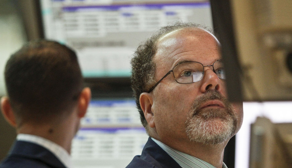 Photo -   FILE- In this Tuesday, July 10, 2012, file photo, Douglas Johnson, a trader for Getco Securities from Levittown, Pa., works during early trading at the New York Stock Exchange. U.S. share futures also pointed down Thursday July 12, 2012 ahead of the New York open. The Dow industrials index was off 0.34 percent in pre-market trading at 12,493.00 and the Standard & Poors 500 fell 0.55 to 1,328.90. ( AP Photo/Bebeto Matthews, File)