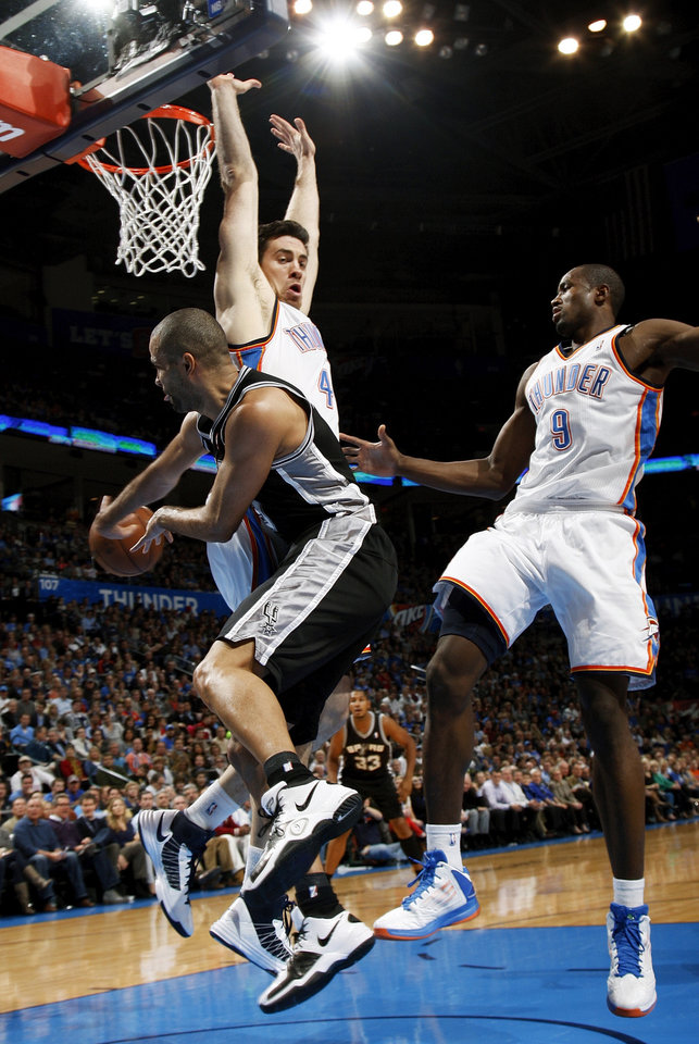 San Antonio's Tony Parker (9) passes away from Oklahoma City's Nick Collison (4) and Serge Ibaka (9) during an NBA basketball game between the Oklahoma City Thunder and the San Antonio Spurs in Oklahoma City Monday, Dec. 17, 2012. Photo by Nate Billings, The Oklahoman