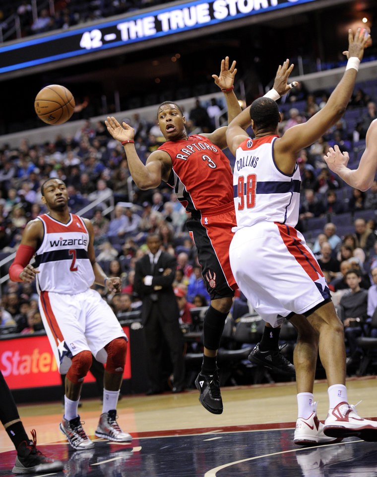 Photo - Toronto Raptors guard Kyle Lowry (3) passes the ball against Washington Wizards' John Wall (2) and Jason Collins (98) during the first half of an NBA basketball game, Sunday, March 31, 2013, in Washington. (AP Photo/Nick Wass)