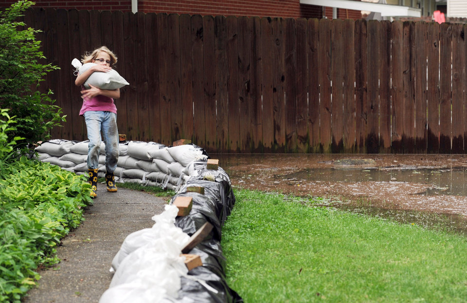 Photo - Clarice Block, 10, struggles as she carries a heavy sandbag down the sidewalk to help her neighbors, P.D. and Aleta Ritchey, sandbag their backyard on Joan Avenue to protect their house after their backyard was flooded from Pigeon Creek in Evansville, Ind. on Wednesday, April 27, 2011. Myra Taber, the Ritchey