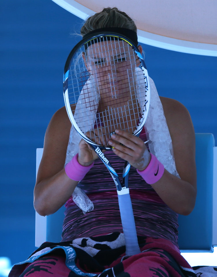 Photo - Victoria Azarenka of Belarus checks strings of her racket during a break in her quarterfinal against Agnieszka Radwanska of Poland during their quarterfinal at the Australian Open tennis championship in Melbourne, Australia, Wednesday, Jan. 22, 2014.(AP Photo/Aaron Favila)