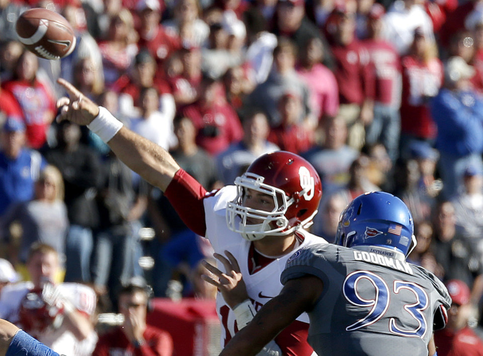 OU's Blake Bell (10) throws a touchdown pass as he is pressured by KU's Ben Goodman (93) during of the college football game between the University of Oklahoma Sooners (OU) and the University of Kansas Jayhawks (KU) at Memorial Stadium in Lawrence, Kan., Saturday, Oct. 19, 2013. OU won 34-19. Photo by Sarah Phipps, The Oklahoman