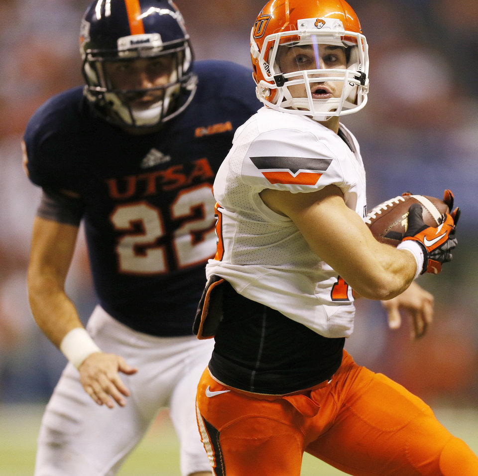Photo - OSU's David Glidden (13) runs after a catch in the second quarter in front of UTSA's Nic Johnston (22) during a college football game between the University of Texas at San Antonio Roadrunners (UTSA) and the Oklahoma State University Cowboys (OSU) at the Alamodome in San Antonio, Saturday, Sept. 7, 2013.  Photo by Nate Billings, The Oklahoman