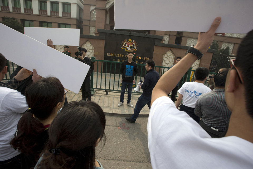 Photo - Relatives of Chinese passengers on board the Malaysia Airlines plane, MH370 hold placards to protest in front of the Malaysia Embassy in Beijing, China, Tuesday, March 25, 2014. Furious over Malaysia's handling of the lost jetliner a day after the country said the passengers must be dead, Chinese relatives of the missing marched Tuesday to the Malaysia Embassy, where they threw plastic water bottles, tried to rush the gate and chanted,
