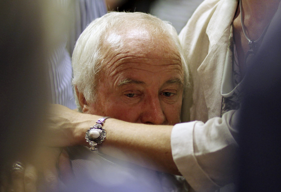Photo - Olympic athlete Oscar Pistorius's father Henke Pistorius is comforted by a unidentified family member during the bail application at the magistrate court in Pretoria, South Africa, Tuesday, Feb. 19, 2013. Pistorius told a packed courtroom Tuesday that he shot his girlfriend to death by mistake, thinking she was a robber. The prosecutor called it premeditated murder. (AP Photo/Themba Hadebe)